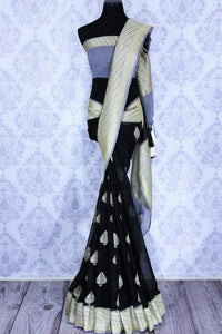 Black georgette Banarasi saree with silver buta for online shopping in USA. The traditional saree is contrasted with a light blue zari border which makes it so captivating. Select from an exquisite collection of traditional Indian Banarasi sarees, designer sarees at Pure Elegance clothing store or shop online.-full view