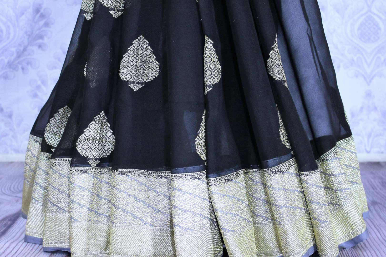 Black georgette Banarasi saree with silver buta for online shopping in USA. The traditional saree is contrasted with a light blue zari border which makes it so captivating. Select from an exquisite collection of traditional Indian Banarasi sarees, designer sarees at Pure Elegance clothing store or shop online.-pleats