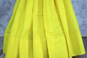 Buy lemon yellow muga Banarasi sari online in USA. The bright saree is a great choice for a classic Indian saree look at special occasions. Select from an exquisite collection of traditional Indian Banarasi sarees, silk sarees at Pure Elegance clothing store or shop online for weddings, parties, and festivals.-pleats
