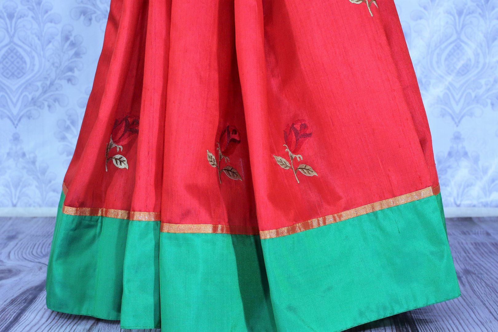 Buy bright red silk sari online in USA with embroidered rose motifs. The saree is an alluring choice for a traditional Indian look at festive occasions.  Buy more such traditional Indian designer silk sarees in USA from Pure Elegance clothing store and keep it ethnic at every occasion.-pleats