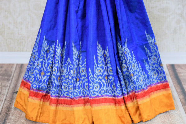 Buy blue ikat silk saree online in USA. Radiate ethnic elegance at special occasions with this absolutely striking ikkat saree with yellow border. Add more such traditional Indian silk saris to your wardrobe, available at Pure Elegance clothing store in USA for women or you can also shop online. -pleats