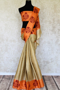Invest in this simple cream tussar silk printed saree with orange pallu. The checks all over the sari further adds to the grace of the nine yards and you can style this beautiful saree with an orange floral printed blouse. Shop handloom sarees, silk saris, printed sari online or visit Pure Elegance store, USA. -full view