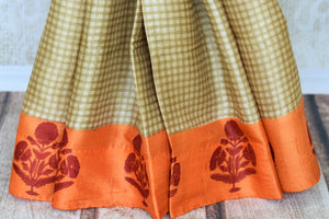 Invest in this simple cream tussar silk printed saree with orange pallu. The checks all over the sari further add to the grace of the nine yards and you can style this beautiful saree with an orange floral printed blouse. Shop handloom sarees, silk saris, printed sari online or visit Pure Elegance store, USA. -pleats