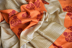 Invest in this simple cream tussar silk printed saree with orange pallu. The checks all over the sari further add to the grace of the nine yards and you can style this beautiful saree with an orange floral printed blouse. Shop handloom sarees, silk saris, printed sari online or visit Pure Elegance store, USA. -details