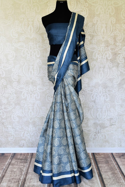 Head to work in style with our exquisitely tailored blue tussar printed saree. It comes with a plain blue blouse. The minimal linear design flowing across the border makes it even prettier. Shop handloom sarees, designer saris, embroidered sarees, ikkat saris, Indian dresses online or visit Pure Elegance store, USA. -full view