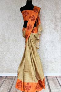 Buy elegant beige printed tussar silk sari online in USA with orange printed border. The saree is an evergreen piece for a regular saree style. If you are looking for Indian handloom sarees in USA, then Pure Elegance is the place for you. Shop online or visit our exclusive fashion store in USA.-full view