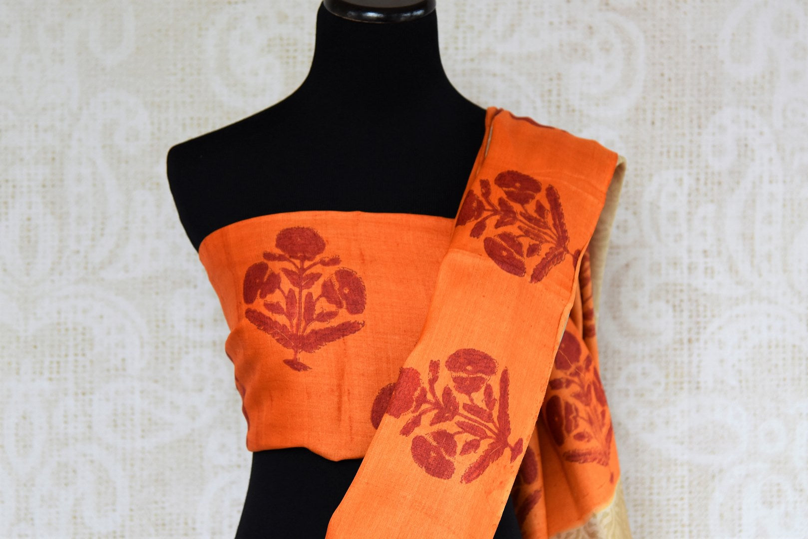 Buy elegant beige printed tussar silk sari online in USA with orange printed border. The saree is an evergreen piece for a regular saree style. If you are looking for Indian handloom sarees in USA, then Pure Elegance is the place for you. Shop online or visit our exclusive fashion store in USA.-blouse pallu