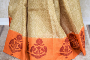 Buy elegant beige printed tussar silk sari online in USA with orange printed border. The saree is an evergreen piece for a regular saree style. If you are looking for Indian handloom sarees in USA, then Pure Elegance is the place for you. Shop online or visit our exclusive fashion store in USA.-pleats