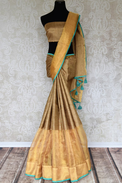 Drape the goodness of this yellow tissue silk sari. The gorgeous broad gold border with turquoise detailing enhances the beauty of this contemporary silk saree. Style this with turquoise silk blouse featuring silver zari work. Shop handloom sarees, silk saris, online or visit Pure Elegance store, USA. -full view