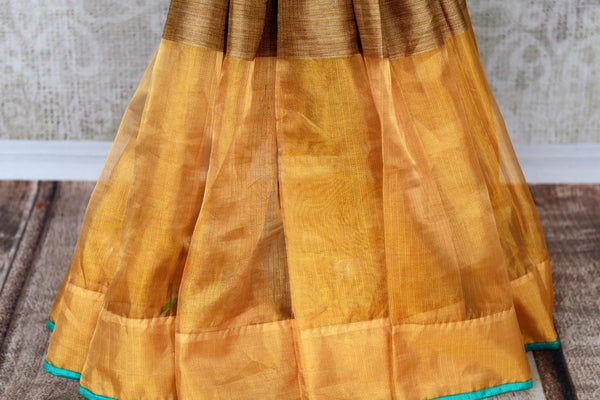 Drape the goodness of this yellow tissue silk sari. The gorgeous broad gold border with turquoise detailing enhances the beauty of this contemporary silk saree. Style this with turquoise silk blouse featuring silver zari work. Shop handloom sarees, silk saris, online or visit Pure Elegance store, USA. -pleats