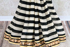 Black and white striped embroidered georgette saree buy online in USA with velvet blouse. Beautifully designed saree is a stylish choice for special occasions. Shop Indian designer sarees with blouses in USA from an alluring collection available at Pure Elegance fashion store.-pleats