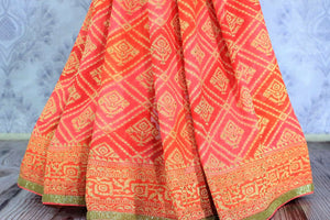 Buy beautiful orange khaddi Banarasi georgette sari online in USA. The saree is a perfect choice for a traditional look at special occasions. Buy more such Indian Banarasi sarees in USA at Pure Elegance exclusive fashion store or shop online at the comfort of your home.-pleats