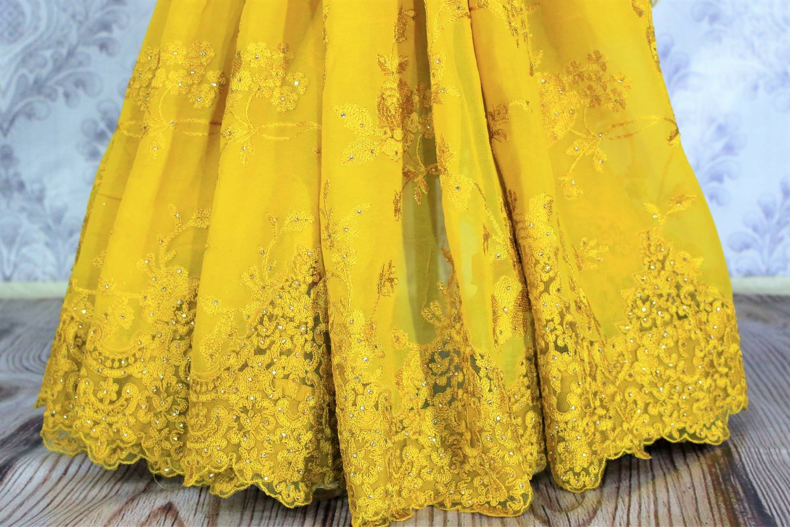 Buy alluring yellow embroidered georgette saree online in USA. Dazzle in this vibrant color saree with delicate embroidery at parties and special occasions. Make your party look special with beautiful Indian designer sarees available at Pure Elegance Indian clothing store in USA or shop online.-pleats