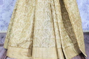 Shop beige embroidered tussar silk saree online in USA with striped pallu. Bring a touch of tradition to your Indian look with an exquisite range Indian handloom saris, pure silk sarees available at Pure Elegance Indian fashion store in USA or shop online.-pleats