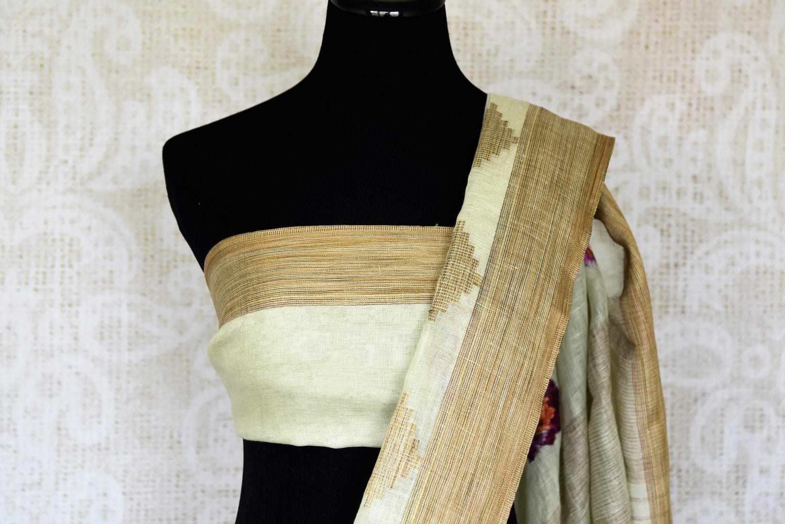 The traditional art form of applique work is beautifully showcased in white linen saree with light brown border all over it. This aesthetically appealing sari is available online and Indian designer saris are in vogue. Shop this season handloom sarees, kanjeevaram silk saris online or visit Pure Elegance store in USA. -blouse pallu