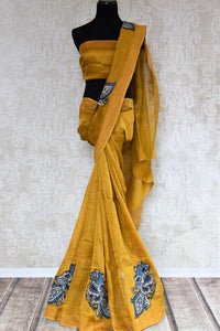 Mustard yellow tussar silk sari for online shopping in USA with peacock Kalamkari applique. Beautifully designed woven sari is a graceful choice for special occasions. Shop Indian handloom sarees, silk saris in USA from an alluring collection available at Pure Elegance fashion store.-full view