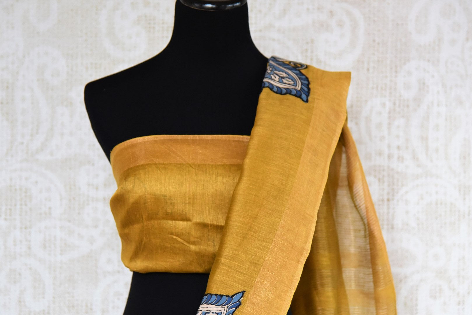 Mustard yellow tussar silk sari for online shopping in USA with peacock Kalamkari applique. Beautifully designed woven sari is a graceful choice for special occasions. Shop Indian handloom sarees, silk saris in USA from an alluring collection available at Pure Elegance fashion store.-blouse pallu