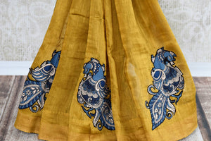 Mustard yellow tussar silk sari for online shopping in USA with peacock Kalamkari applique. Beautifully designed woven sari is a graceful choice for special occasions. Shop Indian handloom sarees, silk saris in USA from an alluring collection available at Pure Elegance fashion store.-pleats