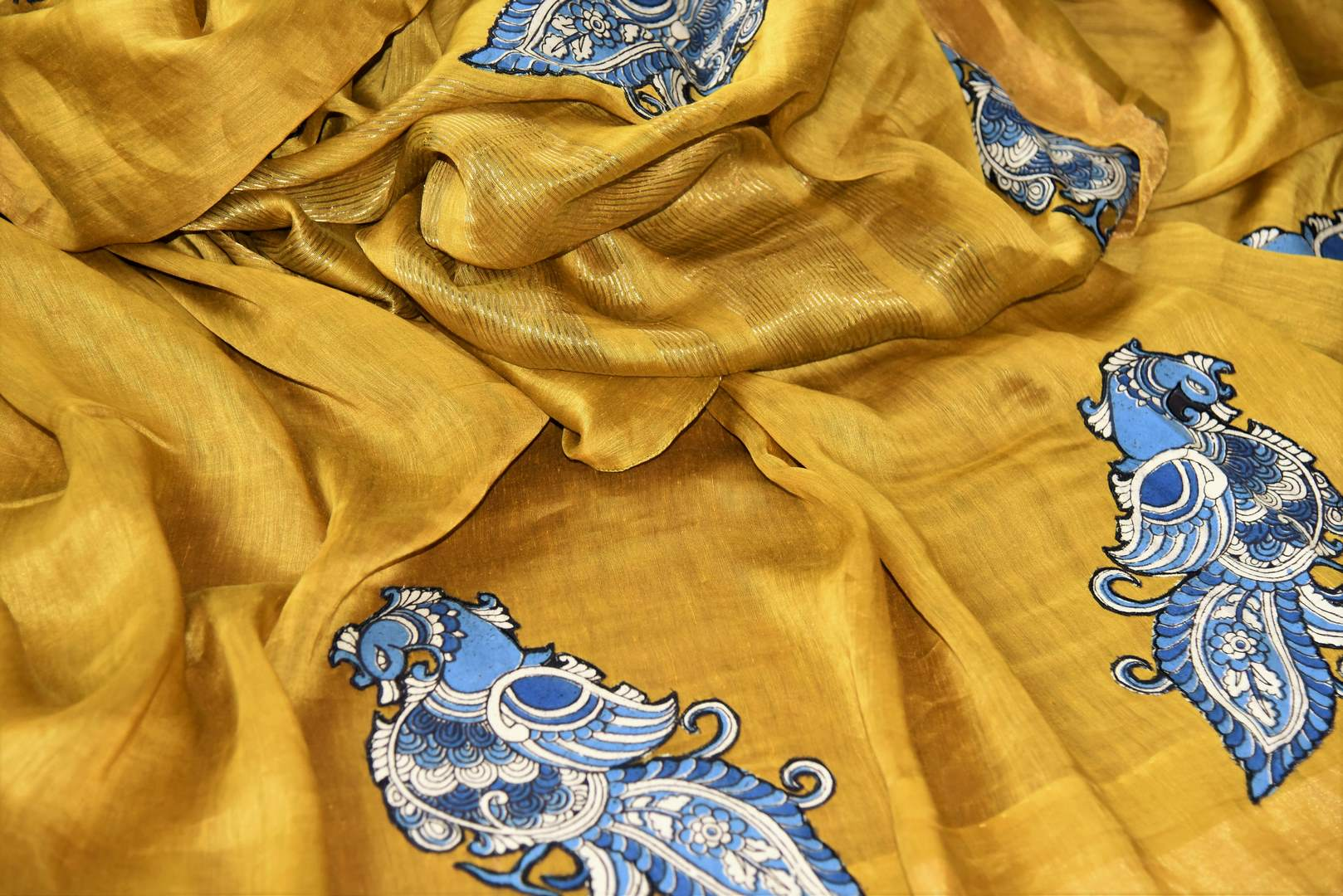 Mustard yellow tussar silk sari for online shopping in USA with peacock Kalamkari applique. Beautifully designed woven sari is a graceful choice for special occasions. Shop Indian handloom sarees, silk saris in USA from an alluring collection available at Pure Elegance fashion store.-details