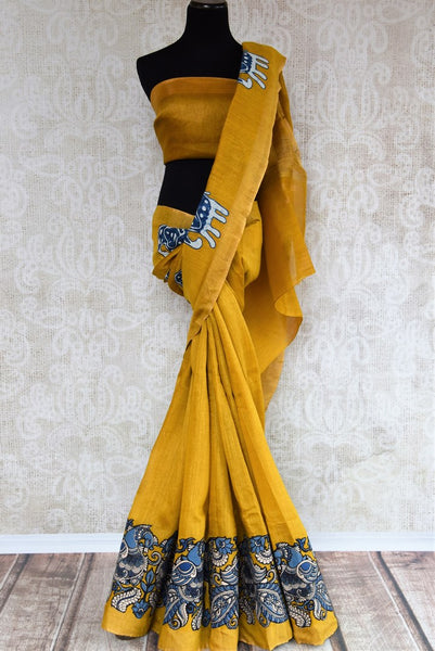 Mustard yellow tussar silk saree for online shopping in USA with Kalamkari applique work. Beautifully designed woven sari is a graceful choice for special occasions. Shop Indian handloom sarees, silk saris in USA from an alluring collection available at Pure Elegance fashion store.-full view