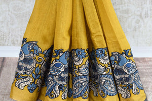 Mustard yellow tussar silk saree for online shopping in USA with Kalamkari applique work. Beautifully designed woven sari is a graceful choice for special occasions. Shop Indian handloom sarees, silk saris in USA from an alluring collection available at Pure Elegance fashion store.-pleats