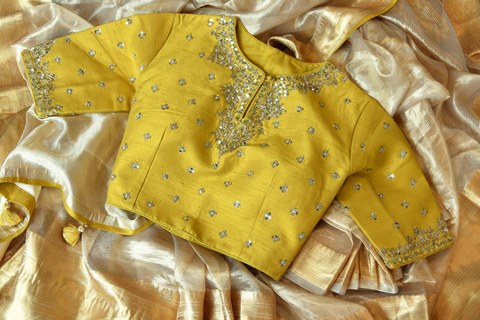 Embrace the royalty as you slip into this cream designer tissue silk saree. The breath-taking details of yellow embroidered blouse featuring intricate embroidery add oodles of grace. Shop handloom sarees, silk sari, banarsi silk saree online or visit Pure Elegance store, USA.-details