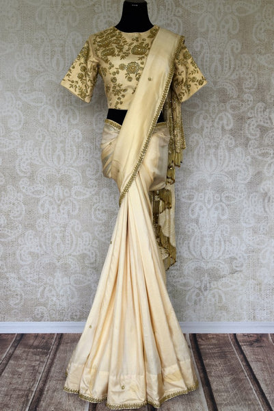 Slay effortlessly in this cream-hued satin and tissue designer silk sari. A perfect party pick, the statement embroidered blouse will steal the hearts away. Shop the beautiful Indian handprinted sarees, designer silk sarees, handblocked saris online or visit Pure Elegance store in USA. -full view