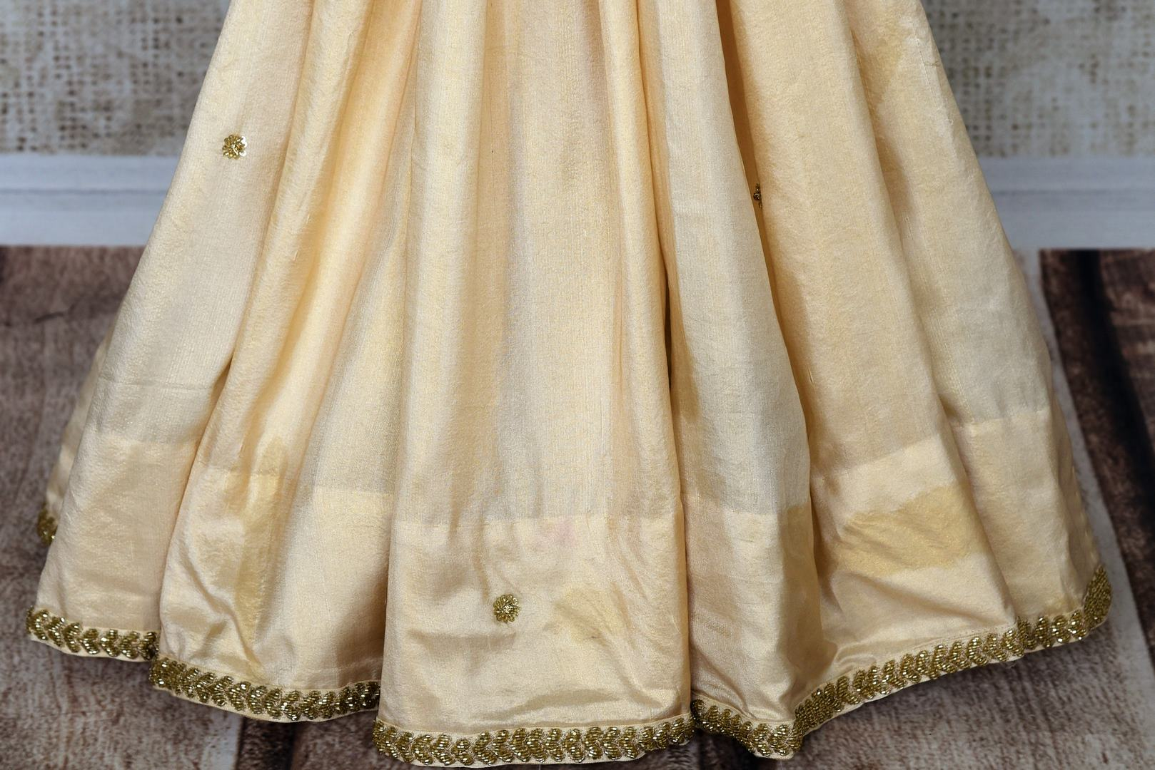 Slay effortlessly in this cream-hued satin and tissue designer silk sari. A perfect party pick, the statement embroidered blouse will steal the hearts away. Shop the beautiful Indian handprinted sarees, designer silk sarees, handblocked saris online or visit Pure Elegance store in USA. -pleats