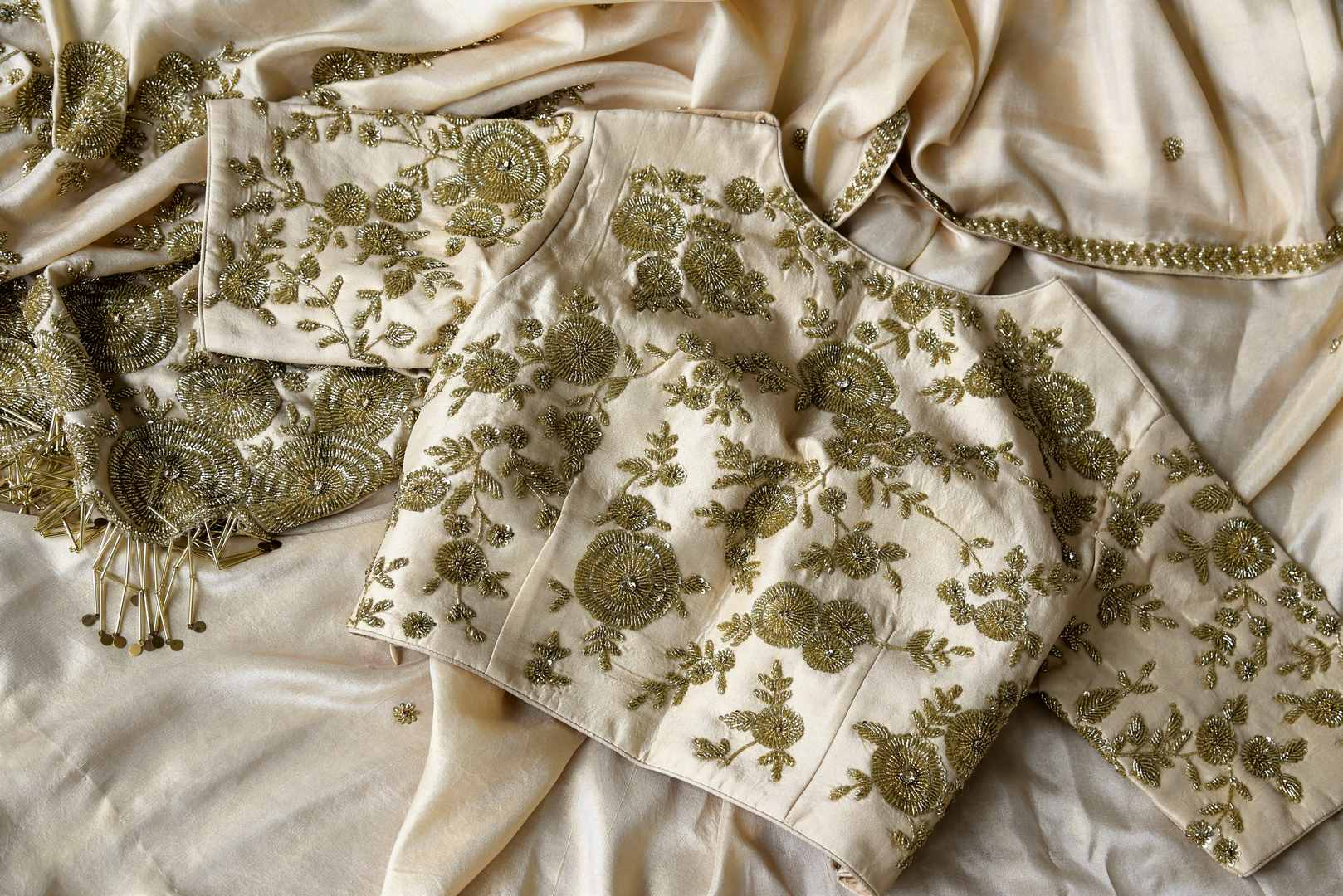 Slay effortlessly in this cream-hued satin and tissue designer silk sari. A perfect party pick, the statement embroidered blouse will steal the hearts away. Shop the beautiful Indian handprinted sarees, designer silk sarees, handblocked saris online or visit Pure Elegance store in USA. -details