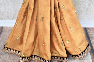 Buy beige embroidered georgette shimmer saree online in USA with velvet blouse. Beautifully designed saree is a captivating choice for weddings and parties. Shop Indian wedding sarees with blouses in USA from an alluring collection available at Pure Elegance fashion store.-pleats