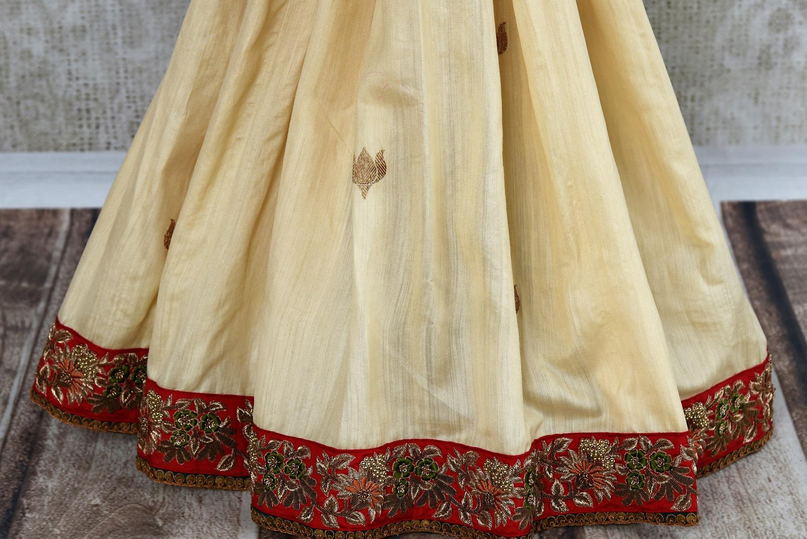 Buy beautiful cream tussar georgette Banarasi saree online in USA with embroidery, The saree is a beautiful drape for a traditional Indian look at weddings. Find more such exquisite Indian designer saris in USA at Pure Elegance Indian fashion store. Shop now.-pleats