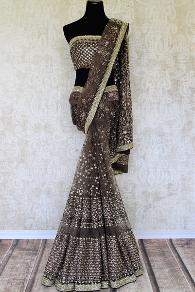 An elaboratively detailed brown sheer net silk saree featuring the intricate art of tikki embroidery all over. Style this breath-taking sari with a designer embroidered blouse and heavily embroidered pallu. Shop handcrafted silk saris, handloom sarees, banarsi silk sarees online or visit Pure Elegance store, USA.-full view