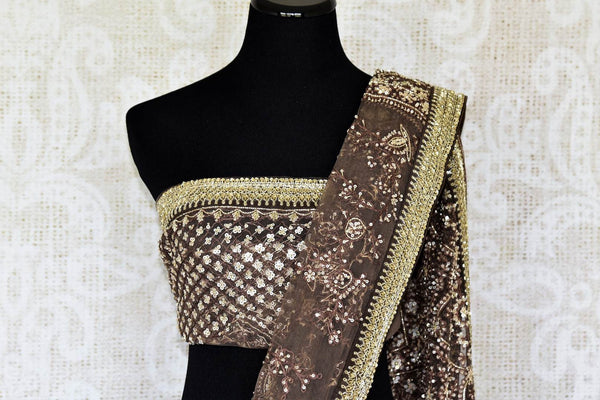 An elaboratively detailed brown sheer net silk saree featuring the intricate art of tikki embroidery all over. Style this breath-taking sari with a designer embroidered blouse and heavily embroidered pallu. Shop handcrafted silk saris, handloom sarees, banarsi silk sarees online or visit Pure Elegance store, USA.-pallu blouse
