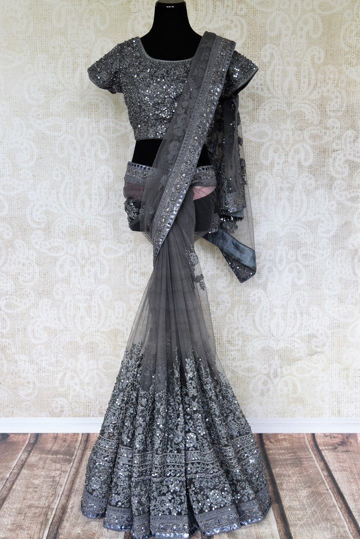 Fall in love with this dreamy grey net sari featuring detailed tikki embroidery threadwork all-over. This gorgeous saree comes with a statement-worthy designer blouse. The floral embroidery and sequins on blouse are quite a fancy. Shop handloom sarees, kanjeevaram silk saris online or visit Pure Elegance store, USA. -full view