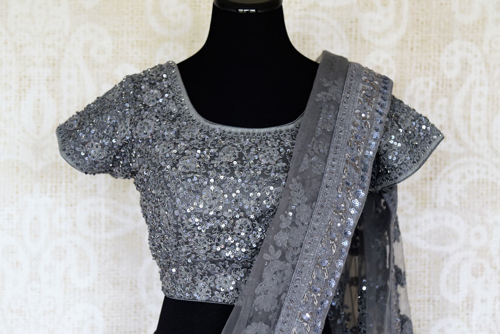 Fall in love with this dreamy grey net sari featuring detailed tikki embroidery threadwork all-over. This gorgeous saree comes with a statement-worthy designer blouse. The floral embroidery and sequins on blouse are quite a fancy. Shop handloom sarees, kanjeevaram silk saris online or visit Pure Elegance store, USA. -blouse pallu