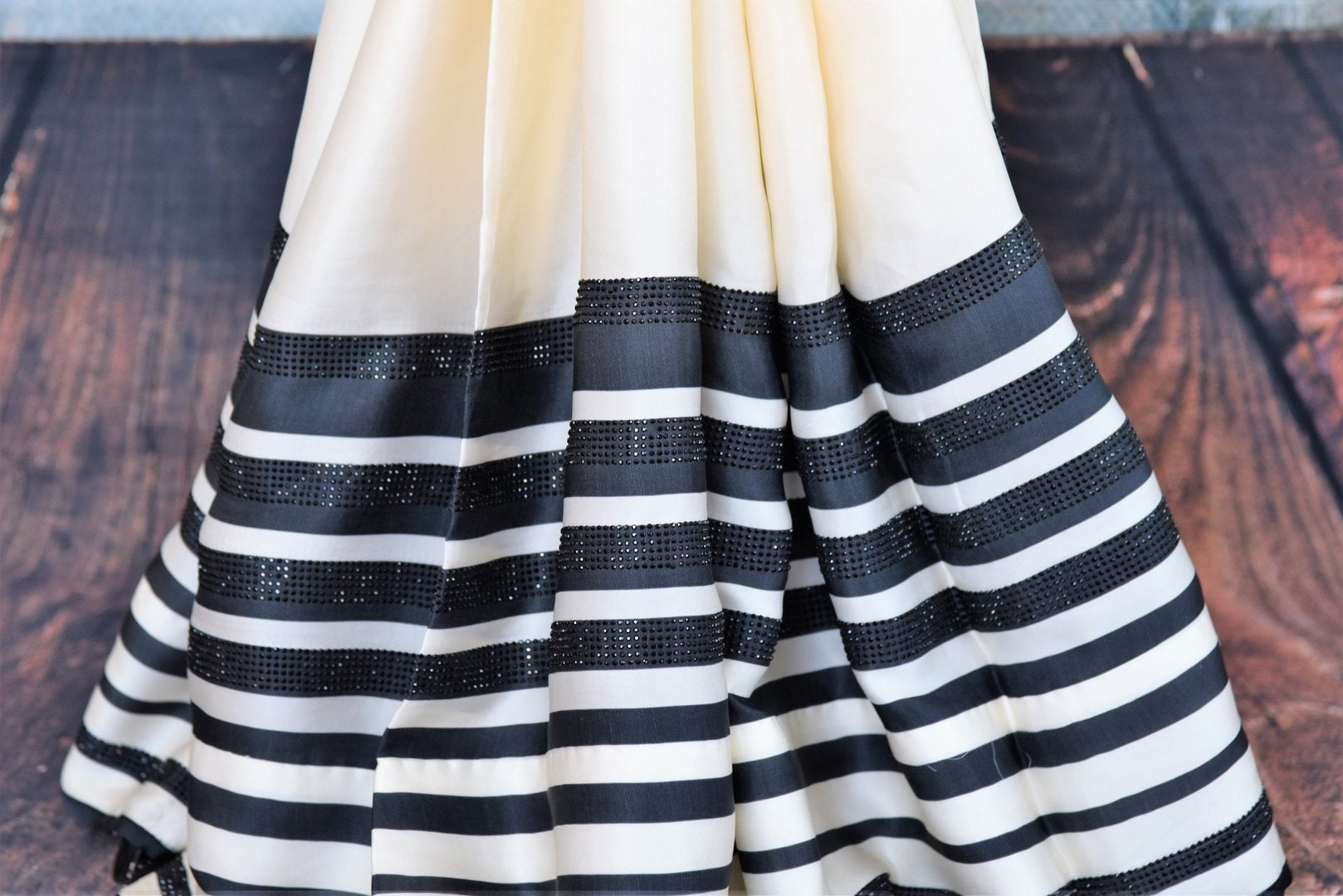 Buy stylish off-white and black stonework striped crepe silk sari online in USA. The saree comes with a matching black blouse piece. Add more such beautiful Indian designer saris to your ethnic wardrobe from Pure Elegance exclusive Indian clothing store in USA or shop online.-pleats