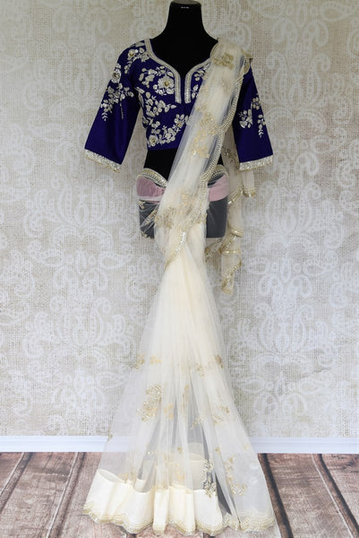 This white net embroidered designer sari is a delicate fusion of style and flamboyance. It comes with a jaw-dropping royal blue silk embroidered designer blouse. Shop such statement silk saris, embroidered sarees, banarsi silk saris online or visit Pure Elegance store in USA.-full view