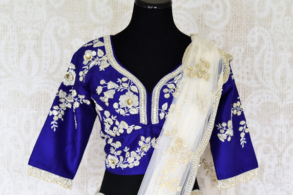 This white net embroidered designer sari is a delicate fusion of style and flamboyance. It comes with a jaw-dropping royal blue silk embroidered designer blouse. Shop such statement silk saris, embroidered sarees, banarsi silk saris online or visit Pure Elegance store in USA.-blouse pallu
