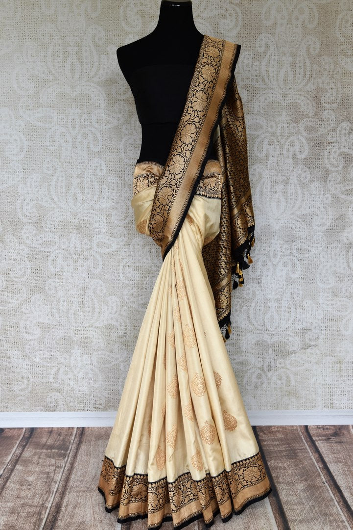 Shop beautifully handcrafted cream banarsi silk sari with buti work all over complemented with a heavy silk pallu and contrasting black blouse. This authentic silk saree is a must-have for every Indian woman. Shop designer silk sarees, handloom saris, Indian dresses online or visit Pure Elegance store in USA. -full view