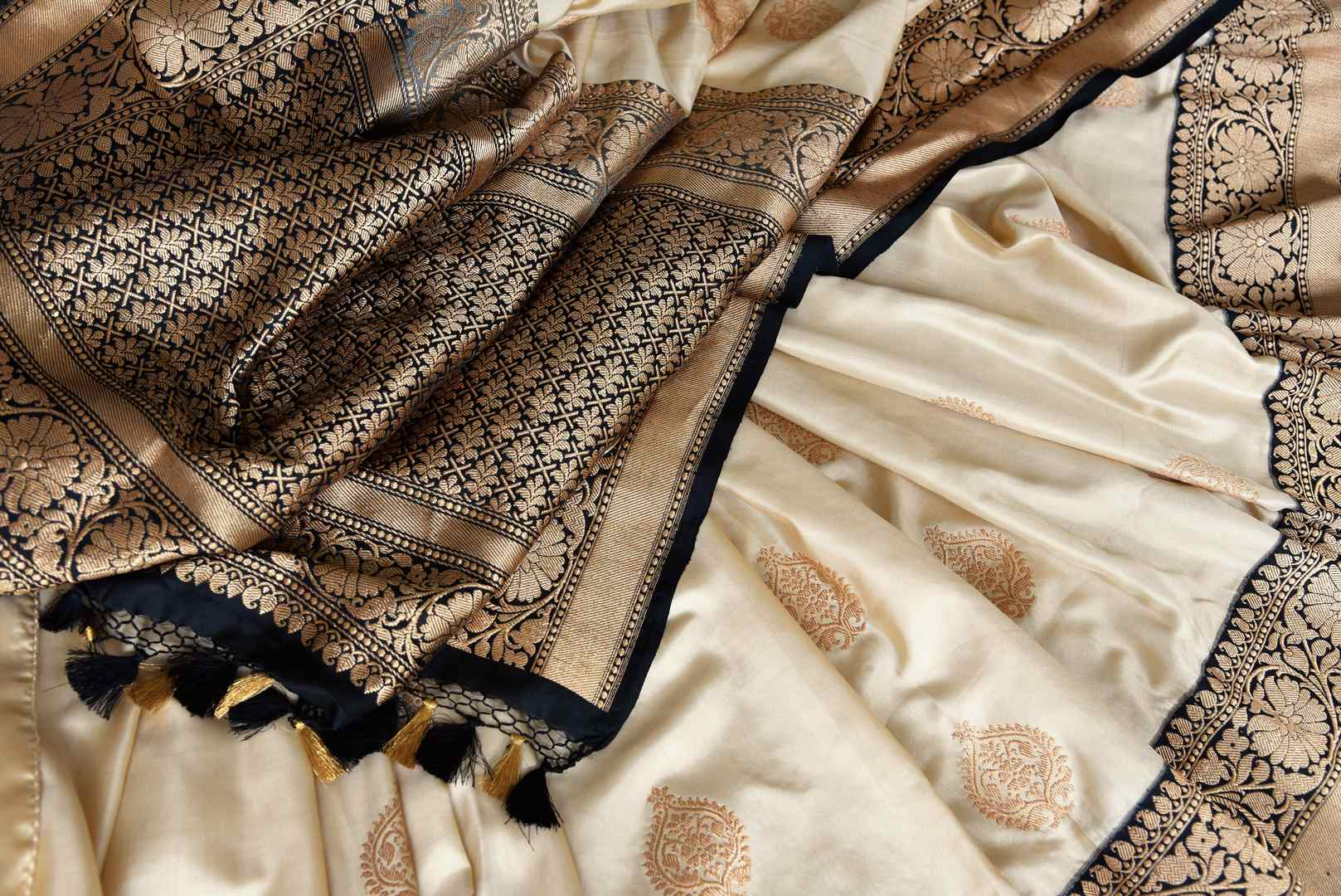 Shop beautifully handcrafted cream banarsi silk sari with buti work all over complemented with a heavy silk pallu and contrasting black blouse. This authentic silk saree is a must-have for every Indian woman. Shop designer silk sarees, handloom saris, Indian dresses online or visit Pure Elegance store in USA. -details