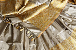 Celebrate festivals and weddings in our modern infused traditional cream banarsi silk saree hand woven to exude perfection and class. The gorgeous ethnic ensemble is handcrafted with authentic and rich silk weaves. Shop designer silk sarees, Indian dresses, handloom saris online or visit Pure Elegance, USA. -details