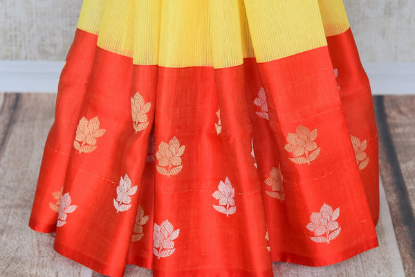 Elevate your style in this yellow cotton banarsi silk saree with a graceful red satin border. The perfect party saree with a winning combination is sure to bring you compliments. It comes with a red contrasting blouse. Shop handloom sarees, silk sarees, designer saris online or visit Pure Elegance store, USA. -pleats