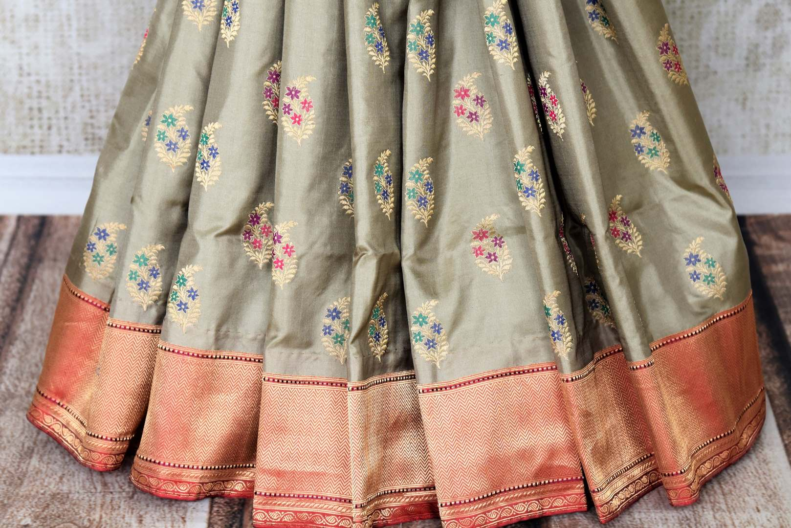 Escalate debonair lady in you with our exquisitely designer grey banarsi silk saree. Style this sari with a red buta work blouse complimented with heavy red pallu to up your style quotient. Shop such designer printed saree, embroidered sari, kanjeevaram silk sari online or visit the Pure Elegance store in USA. -pleats