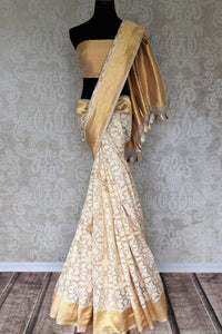 Adorn the beauty of this designer cream tissue banarsi sik saree. Style this breath-taking silk sari with a gold designer blouse complimented with gold pallu. Shop designer silk saris, kalamkari sarees, banarasi silk saris online or visit Pure Elegance store in USA.-full view