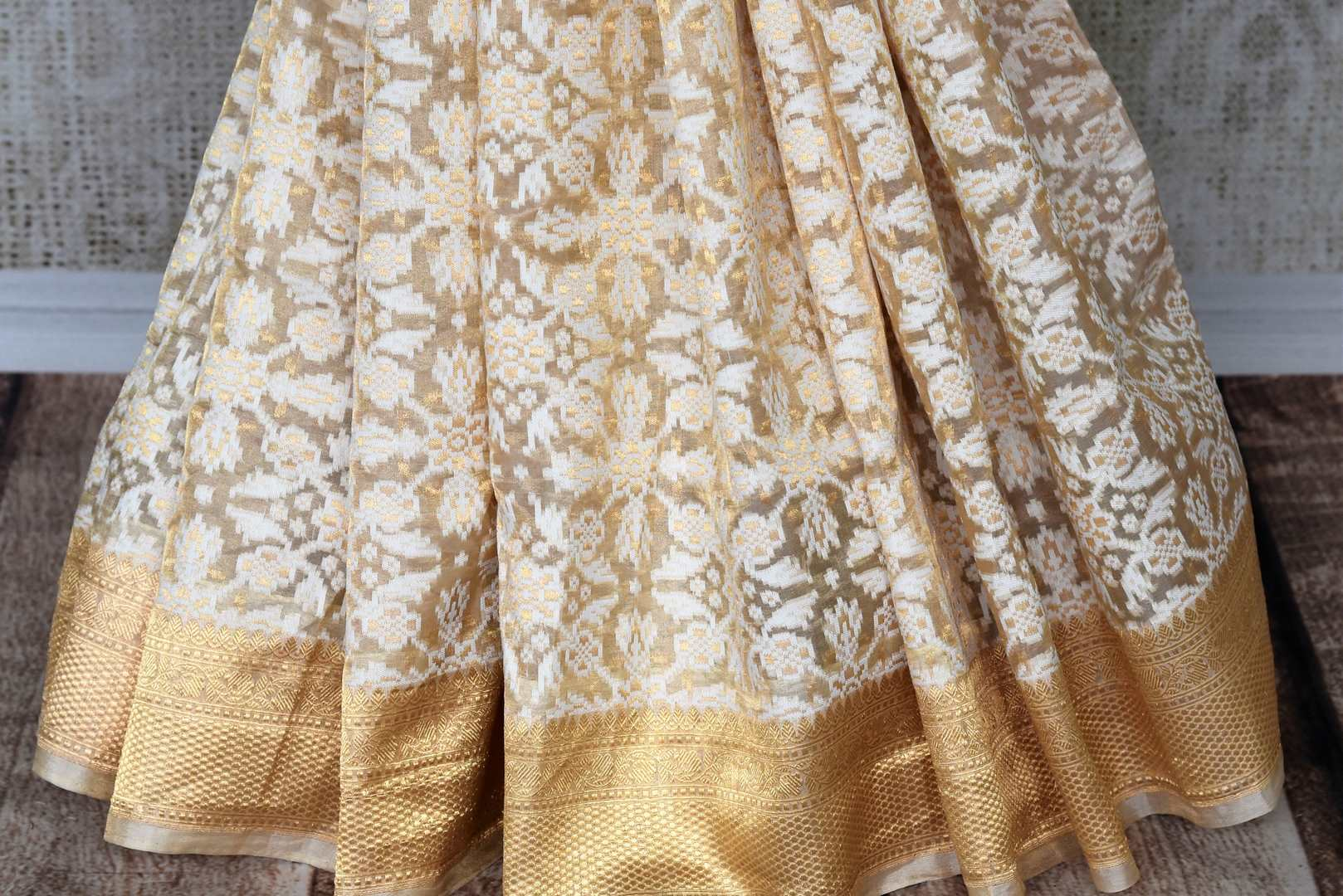 Adorn the beauty of this designer cream tissue banarsi sik saree. Style this breath-taking silk sari with a gold designer blouse complimented with gold pallu. Shop designer silk saris, kalamkari sarees, banarasi silk saris online or visit Pure Elegance store in USA.-pleats