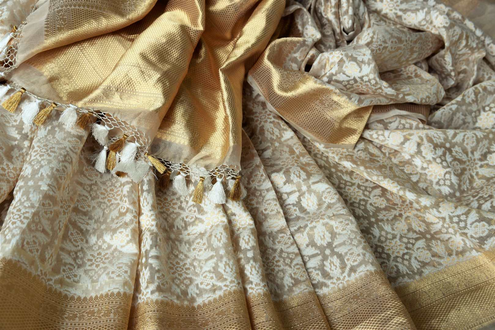 Adorn the beauty of this designer cream tissue banarsi sik saree. Style this breath-taking silk sari with a gold designer blouse complimented with gold pallu. Shop designer silk saris, kalamkari sarees, banarasi silk saris online or visit Pure Elegance store in USA.-details