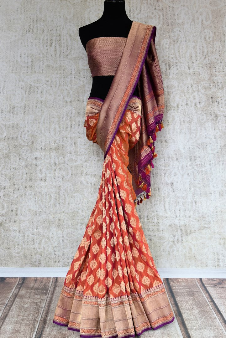 Buy online traditional orange Banarasi silk sari with buta online in USA and purple zari border. The saree is a beautiful drape for an ethnic Indian look at weddings and special occasions. Find more such exquisite Indian silk sarees, handloom sarees in USA at Pure Elegance Indian fashion store. Shop now.-full view