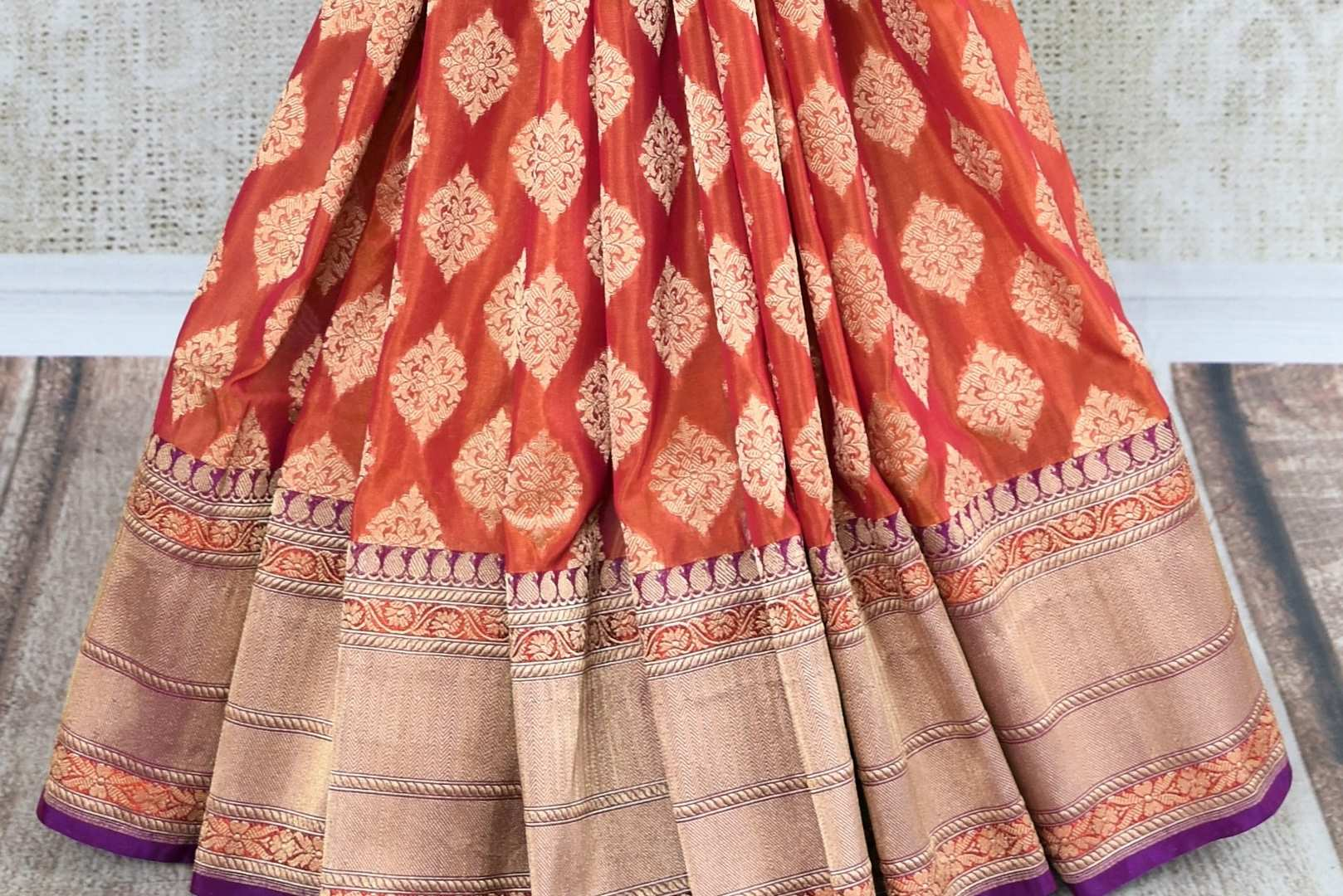 Buy online traditional orange Banarasi silk sari with buta online in USA and purple zari border. The saree is a beautiful drape for an ethnic Indian look at weddings and special occasions. Find more such exquisite Indian silk sarees, handloom sarees in USA at Pure Elegance Indian fashion store. Shop now.-pleats