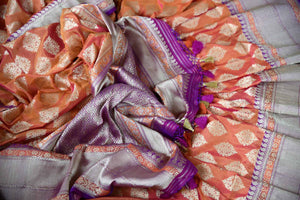 Buy online traditional orange Banarasi silk sari with buta online in USA and purple zari border. The saree is a beautiful drape for an ethnic Indian look at weddings and special occasions. Find more such exquisite Indian silk sarees, handloom sarees in USA at Pure Elegance Indian fashion store. Shop now.-details