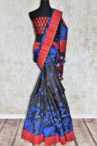 Channel contemporary vibes in this exclusively designed black kora tissue silk with banarsi weave. It comes with a red silk contrasting border and floral work. Style this sari with red and black silk blouse. Shop handloom saris, chiffon sarees, printed sari online or visit Pure Elegance store, USA.-full view
